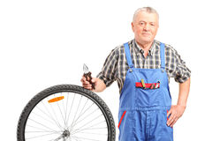 Mature mechanic standing by a bicycle wheel Royalty Free Stock Photography