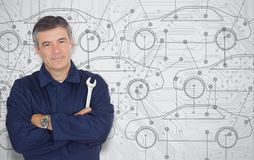 Mature mechanic standing in front of a cars diagram background Royalty Free Stock Photos