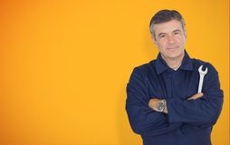 Mature mechanic standing in front of yellow background Stock Images