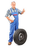 Mature mechanic with tyre Stock Photo