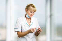 Mature medical female doctor looking on thermometer. Royalty Free Stock Images