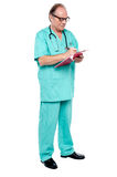 Mature medical practitioner writing case history of a patient Royalty Free Stock Photo