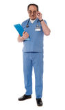 Mature medical professional, full length. Medical professional looking at camera while holding his eyeglasses Royalty Free Stock Photos
