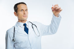 Mature medical worker posing with blood sample in test tube. Up and coming professional. Waist up shot of a serious doctor looking into the camera confidently royalty free stock photography