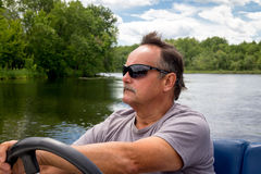 Mature men driving motor boat in a river Stock Photography