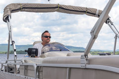 Mature men driving a pontoon boat on a lake Stock Photo
