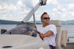 Mature men driving a pontoon boat on a lake Royalty Free Stock Photos