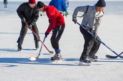 Mature men fighting for the pack while playing hockey on a frozen river Dnepr. Dnepr, Ukraine - January 22, 2017: Mature men fighting for the pack while playing royalty free stock image