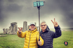 Mature men friends take a selfie in the Stonehenge archaeologica Royalty Free Stock Image