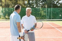 Mature men holding rackets while talking on tennis court during summer weekend royalty free stock photography