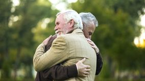 Mature men hugging, happy to see each other, old friends meeting, greeting. Stock photo stock images