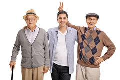 Mature men pranking a young guy with bunny ears Royalty Free Stock Photography