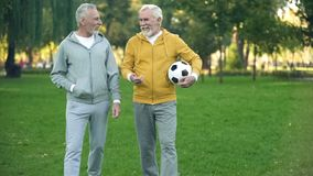 Mature men in sportswear walking in park with ball, sport hobby, health care. Stock photo royalty free stock photos