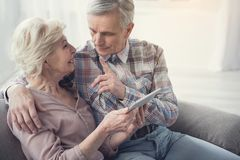 Enamored senior couple spending time in communication. Mature men talking to his wife and showing forefinger while she is holding tablet and looking at him with Royalty Free Stock Image