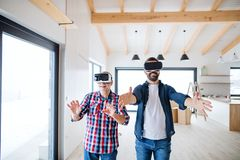 A man with VR goggles and his senior father furnishing new house, a new home concept. royalty free stock images