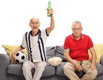 Mature men watching football. Two mature men watching football and cheering for a different team isolated on white background Royalty Free Stock Photos