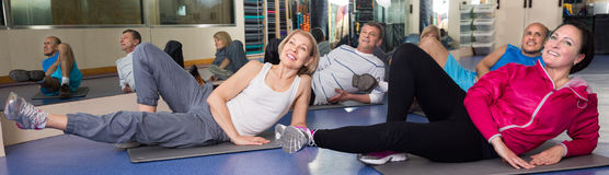 Mature men and women are engaged on mat in gym. Happy mature men and women are engaged on mat in gym. focus on the left woman stock photo