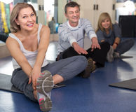 Mature men and women are engaged on mat in gym. Ordinary mature men and women are engaged on mat in gym stock images