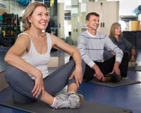 Mature men and women are engaged on mat in gym. Mature men and women are engaged on mat in modern gym stock images
