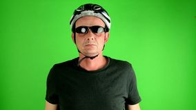 Mature mid aged man. Portrait of a mature cyclist in front of green screen. Man wears sunglasses, sport helmet and stock video footage