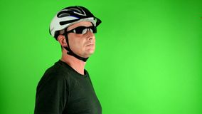 Mature mid aged man. Portrait of a mature cyclist gives thumb up in front of green screen. Man wears sunglasses, sport stock video footage