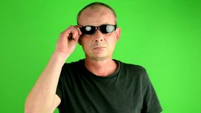 Mature mid aged man walks. Portrait of a mature white man goes in front of green screen. Man wears sunglasses. stock video footage
