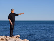 Mature middle-age man standing on a rock pointing. Mature middle-aged man standing on a rock at the coast pointing towards copyspace over a calm blue ocean on a Stock Images
