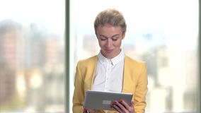 Mature middle aged businesswoman in yellow suit with tablet. Portrait of caucasian woman with modern device indoor, blurred window background stock video footage