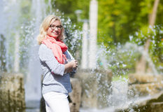 Mature Middle Aged smiling Blond Woman Wearing Spectacles. Portrait of Mature Middle Aged smiling Blond Woman Wearing Spectacles Posing Outdoors in Park.Hands Stock Photo