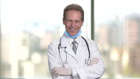 Mature middle aged smiling doctor folding arms. stock video