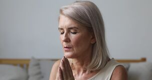 Mature middle aged woman praying with hope at home