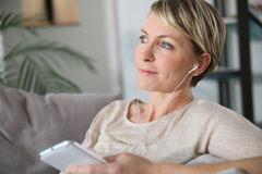 Mature middle-aged woman relaxing on sofa Stock Images