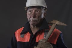 Mature miner covered in coal dust holding a pick axe. Taken on a black background stock image