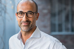 Mature mixed race man smiling. Portrait of happy mature man wearing spectacles and looking at camera outdoor. Man with beard and glasses feeling confident. Close Stock Photos