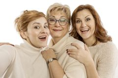Mature mom with adult daughters laugh and take pictures stock photography