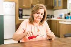 Mature mom filling a spoon with syrup Royalty Free Stock Images