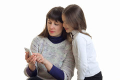 Mature mom shows her little daughter pictures in my phone Royalty Free Stock Photos