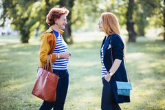 Mature mother and adult daughter enjoying in the park royalty free stock image
