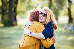 Mature mother and adult daughter hugging in the park royalty free stock images