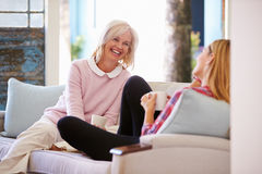 Mature Mother With Adult Daughter Relaxing On Sofa At Home Stock Photos