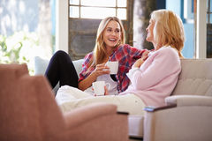 Mature Mother With Adult Daughter Relaxing On Sofa At Home Stock Image