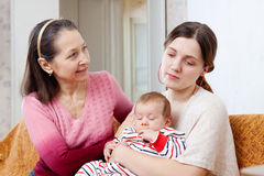 Mature mother asks for forgiveness from adult daughter. With baby after quarrel at home royalty free stock photo