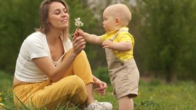 Mature mother calls to her baby and teaches him to blow the seeds from dandelions. Happy family in the park at a picnic.  stock video footage