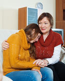 Mature mother comforting crying adult daughter. In home Stock Photography