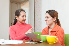Mature mother and daughter is calculates the family budget Royalty Free Stock Photo