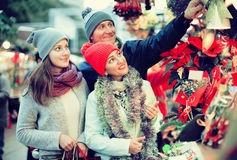 Mature mother, father and teen girl buying red Euphorbia and  fl Stock Image
