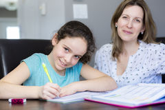 Mature mother helping her child with homework at home. Stock Photos