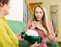 Mature mother presenting gift in box to happy daughter Stock Photography