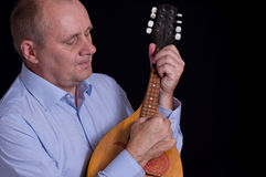 Mature musician playing with mandolin. Portrait of mature musician playing with mandolin Royalty Free Stock Photos