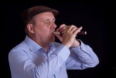Mature musician playing Ukrainian woodwind instrument sopilka Stock Photos